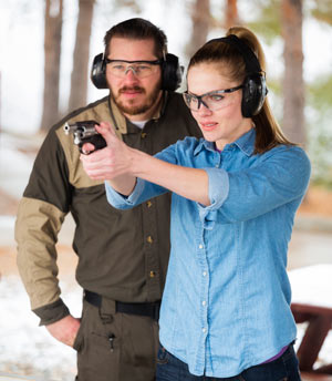 woman shooting gun at range learn to shoot combo class